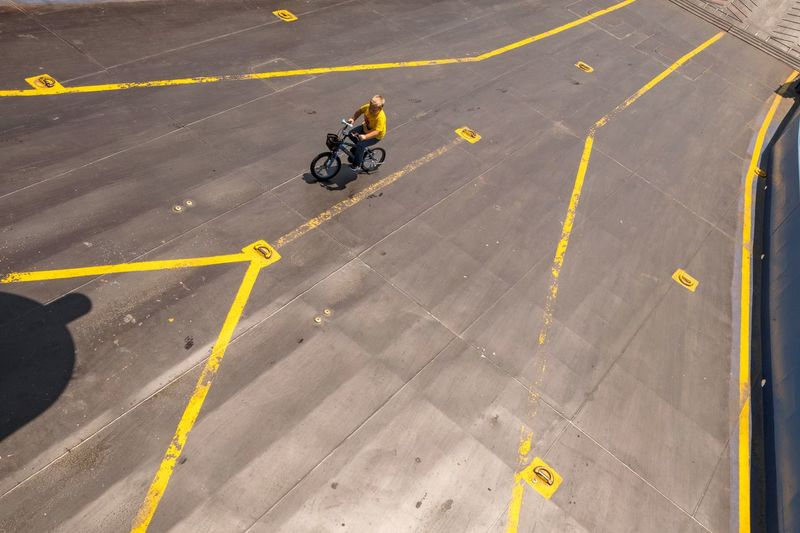 High angle view of yellow riding bicycle on road