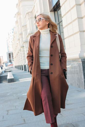 Young woman wearing long coat walking on sidewalk in city