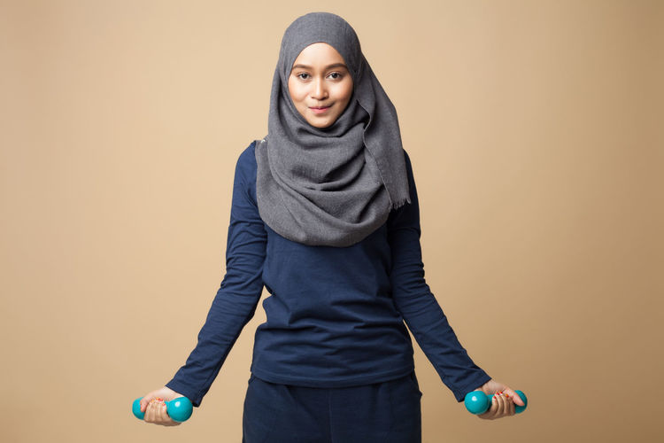 A young beautiful hijab woman is doing exercise with dumbbells on a yellow background Adult Beautiful Woman Beauty Day Front View Hood - Clothing Hooded Shirt Leisure Activity Lifestyles Looking At Camera One Person People Portrait Real People Studio Shot Young Adult Young Women