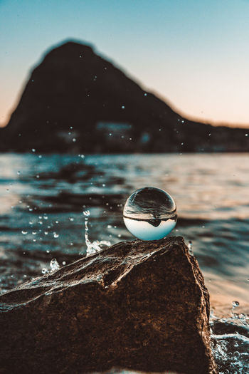 Close-up of crystal ball on rock by sea