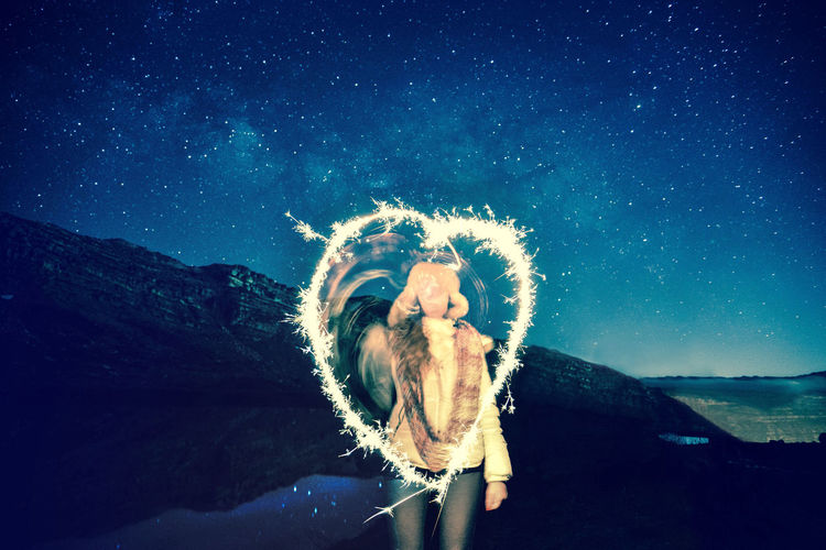 Woman making heart shape with sparklers against star field at night
