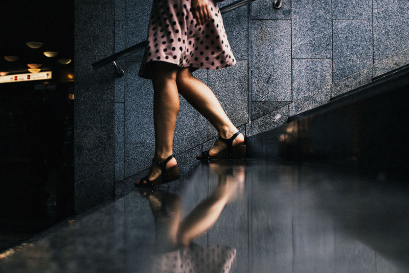 Low section of woman walking on steps by reflection