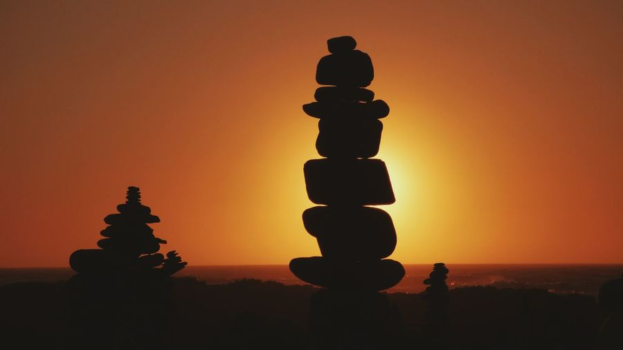 Silhouette Of Stack Against Sunset Sky