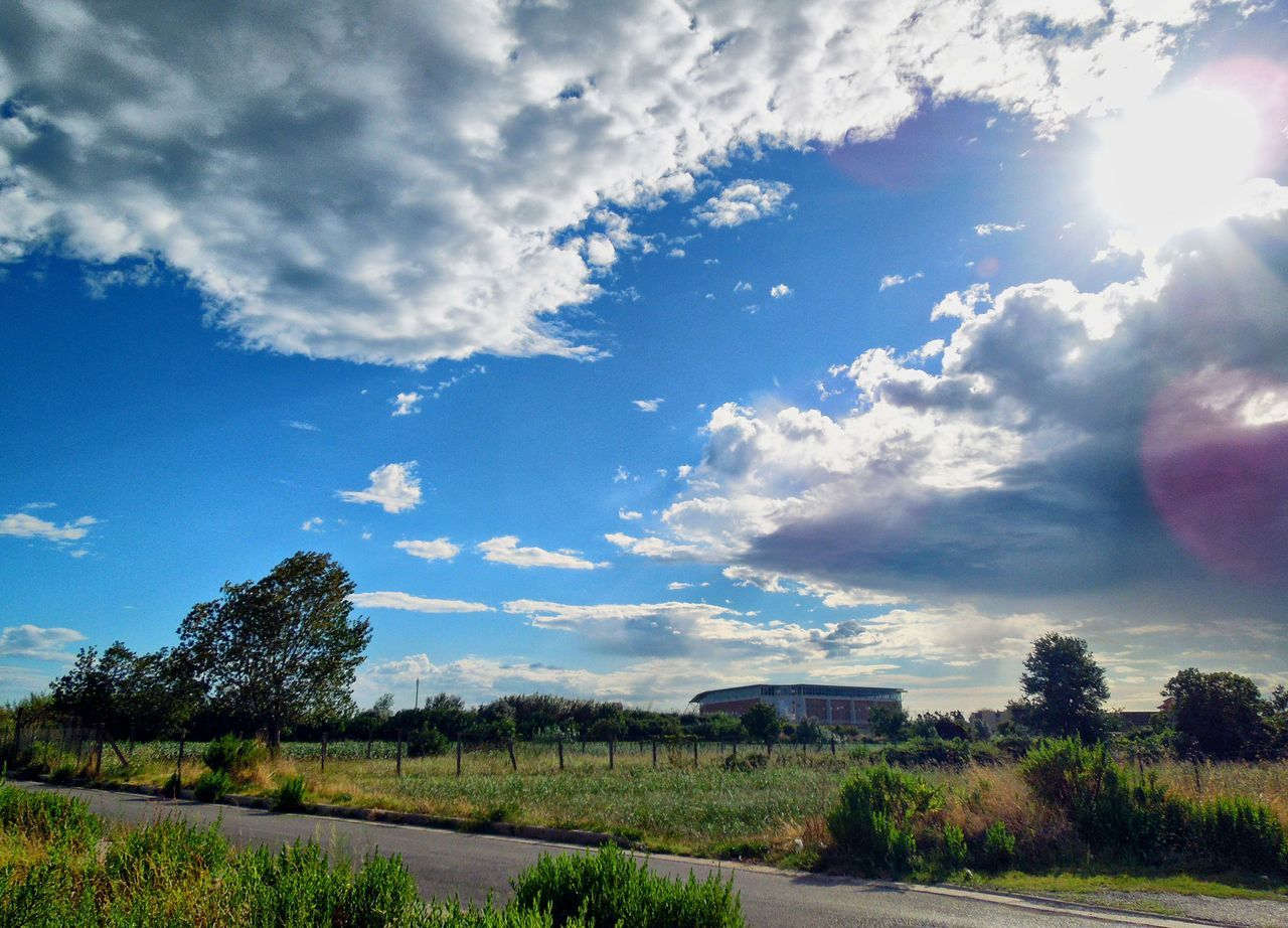 sky, cloud - sky, tree, no people, tranquil scene, day, landscape, scenics, outdoors, nature, sunlight, tranquility, beauty in nature, built structure, grass, architecture