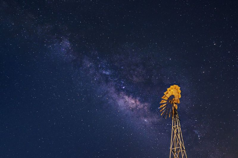 Low angle view of windmill against star field