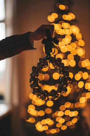 Close-up of hand holding illuminated christmas lights