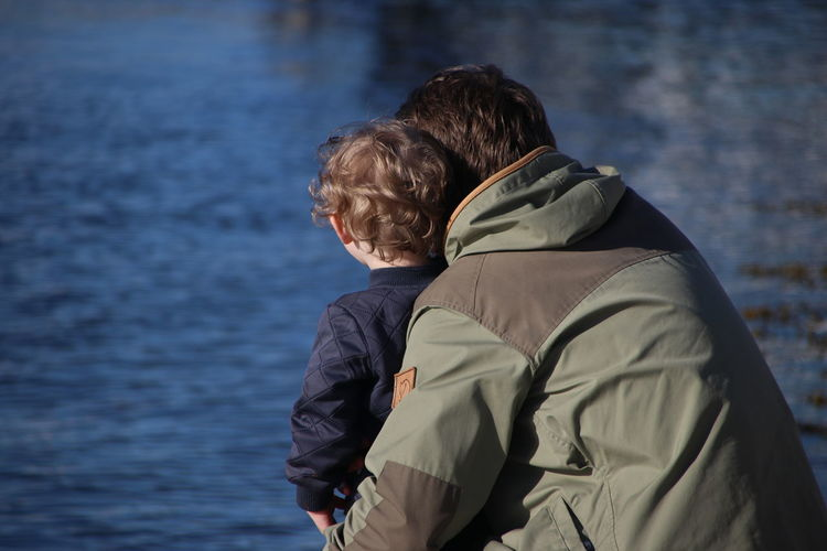 Rear view of father and son at sea shore