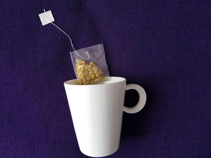 camomile tea in a mug Mug Camomile Camomile Tea Relaxing Purple Food And Drink Purple Background Herbal Tea Tea Leaves