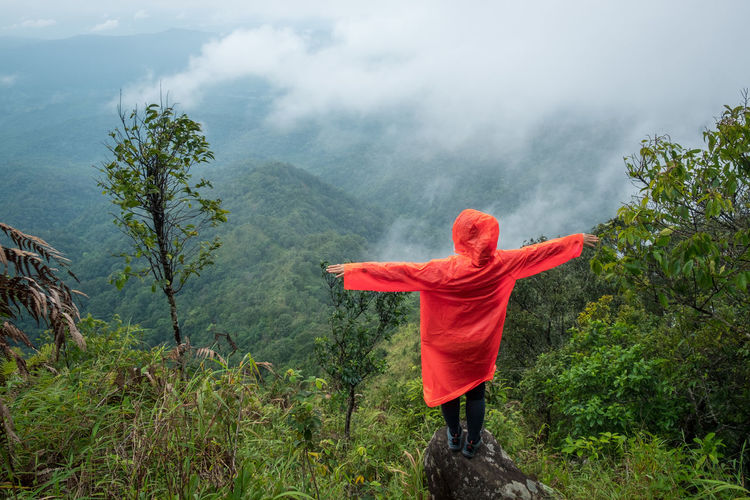 Rear view of woman with arms outstretched wearing red raincoat standing on cliff