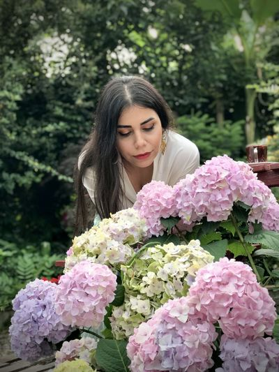 Beautiful young woman with pink flowers against plants