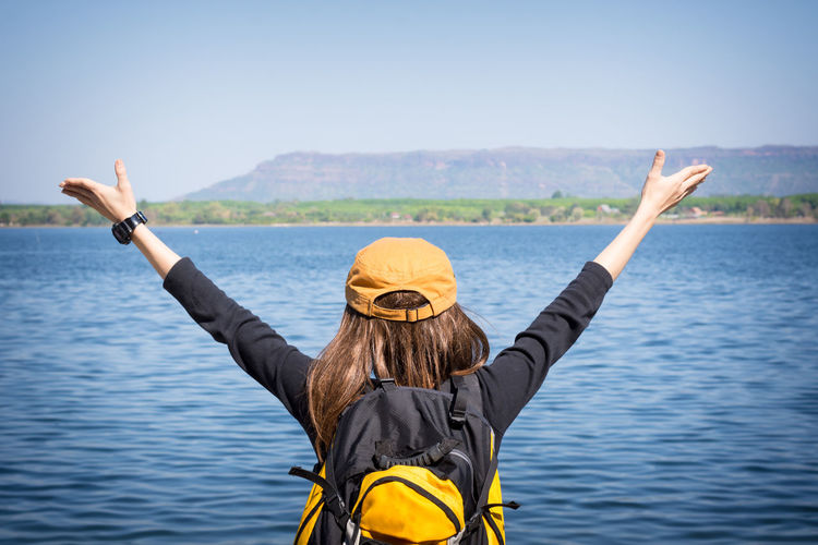 Rear view of backpack woman with arms raised standing by lake against clear sky