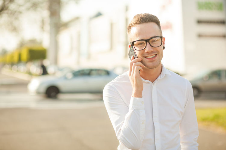 Portrait of young man talking on smart phone while standing in city