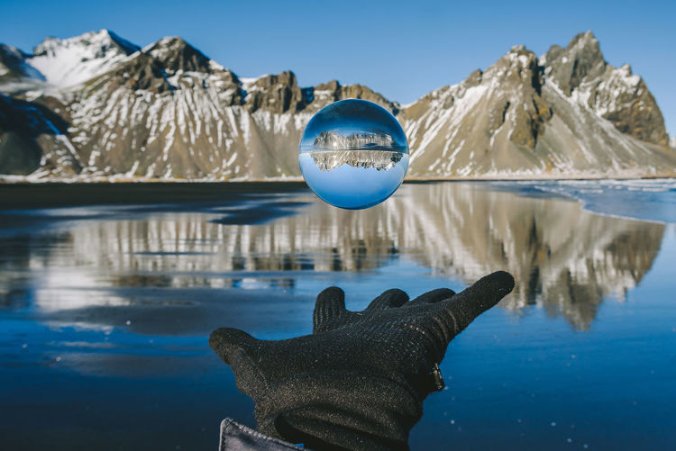 Cropped Hand With Crystal Ball In Mid-Air Against Lake And Mountain
