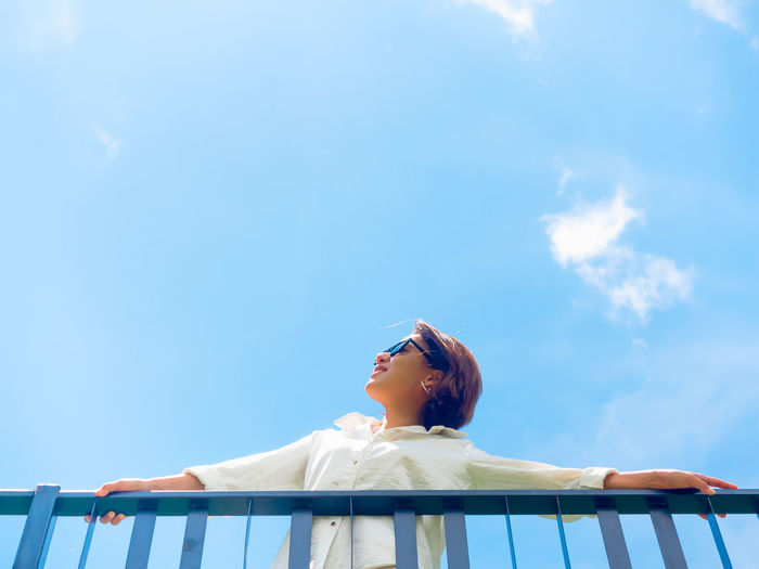 Low angle view of woman looking away against blue sky