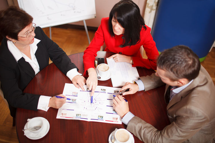 , Group Adults Audience Business Businessman Businesswoman Caucasian Colleagues Discussing Executivesuite Group Man Office Partners People Pointing Statistics  Three Women