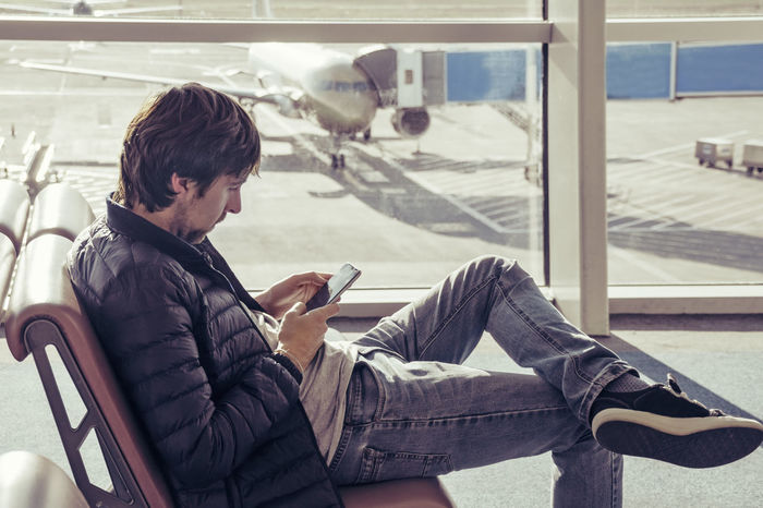 Young caucasian man in jeans and outerwear is sitting in chair airport waiting hall and using smartphone. Online remote banking, hotel booking, mobility, reading news, use of 3 G and 4 G internet networks. Traveling people. Airplane with jetway at background. Man Mobile Phone Plane Waiting Waiting Hall Addiction Airplane Airport Casual Clothing Communication Connection Gadget Internet Leisure Activity Lifestyles Message Networking Seat Side View Sitting Technology Time Wifi Wireless Technology Young Adult