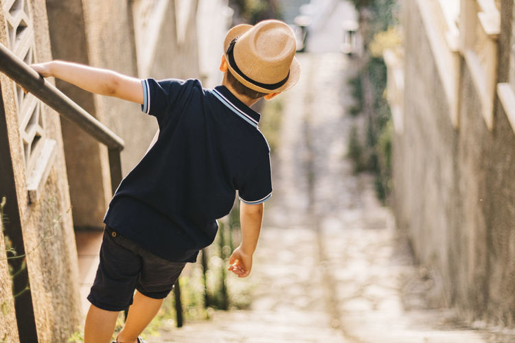 Rear view of boy wearing hat standing on staircase by railing outdoors