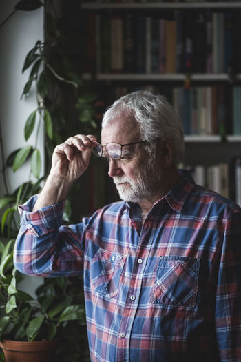 Thoughtful senior therapist standing by potted plant at home office