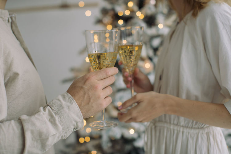 Midsection of couple holding champagne flutes while standing by christmas tree at home