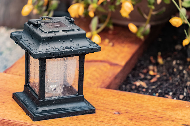 The solar lantern. Droplets Beauty In Nature Black Color Close-up Closeup Day Decoration Field Fire Focus On Foreground Garden Garden Decor High Angle View Metal Nature No People Old Outdoor Decor Outdoors Solar Lantern Still Life Sunlight Table Technology Wet Wood Wood - Material