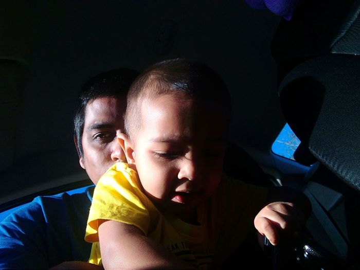 Portrait of mid adult man with son in car