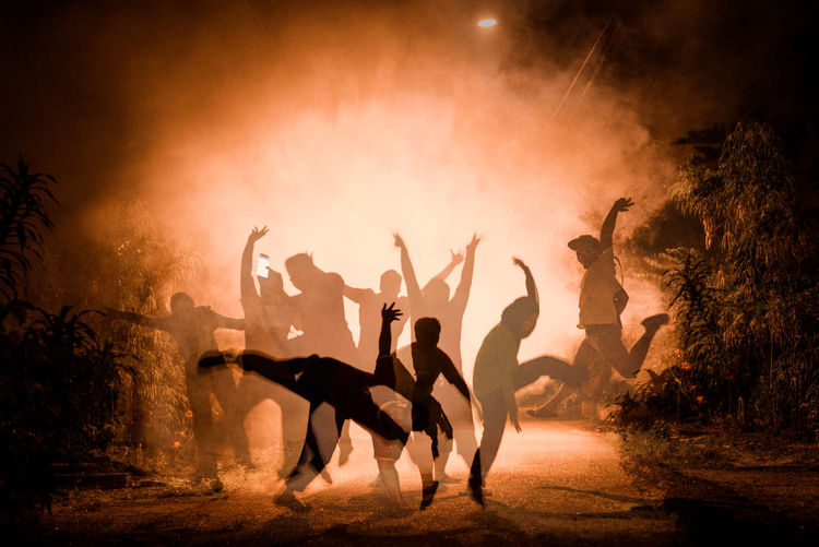 Digital composite image of people jumping over street in foggy weather at night