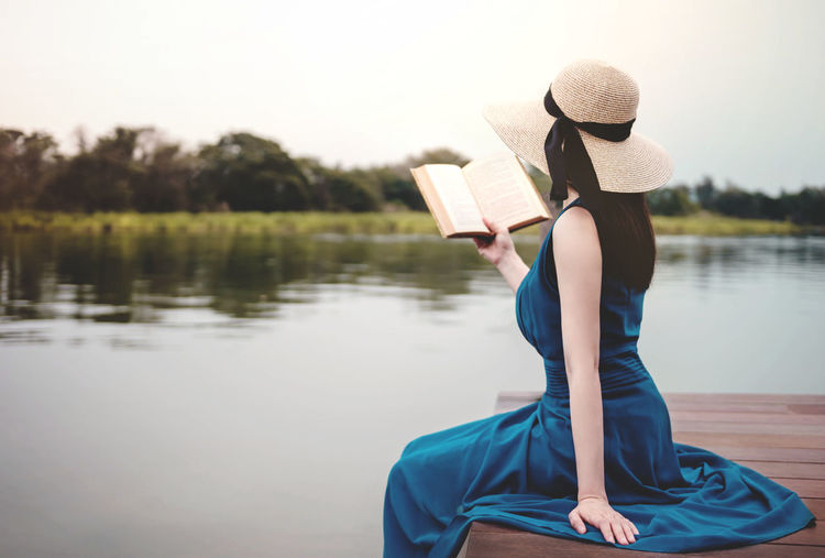 Young Woman Relaxing by Riverside. Sitting on Deck and Reading Book. Unplugged Life Concept Water Hat One Person Lake Clothing Leisure Activity Real People Holding Lifestyles Women Sitting Adult Nature Tranquility Young Adult Beauty In Nature Book Publication Outdoors Relaxation Reading A Book Calm Lady Vintage Park Riverside Relaxing Resting Nature Retro Well Dressed Novel Studying