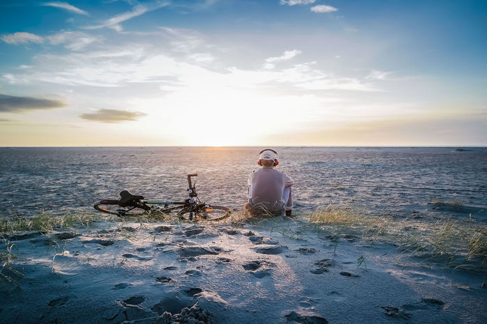 a man sitting with his bike and listen to some music Adult Beach Beachphotography Beauty In Nature Biclycle Bike Day Horizon Over Water Listening To Music Men Music Nature Outdoors People Real People Relaxing Scenics Sea Sitting Sitting Sky Sunset Trave; Vacations Water Live For The Story Live For The Story The Great Outdoors - 2017 EyeEm Awards EyeEmNewHere Creative Space