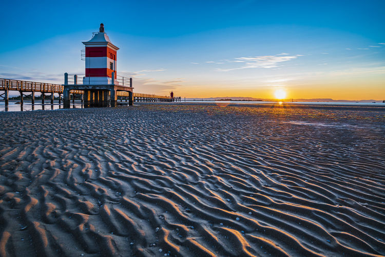 The sun rises over the calm waters of lignano sabbiadoro. explosion of colors on the red lighthouse.