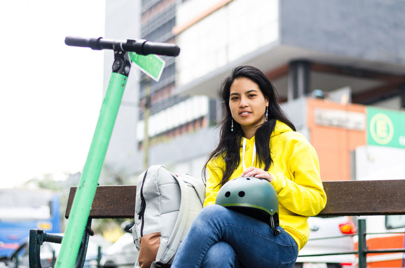 Portrait of woman sitting on bench in city