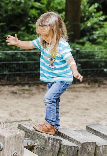 Girl balancing on wooden blocks at park