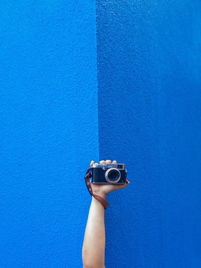 Cropped image of person holding vintage camera against blue wall