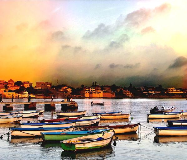 Boats moored in marina at sunset