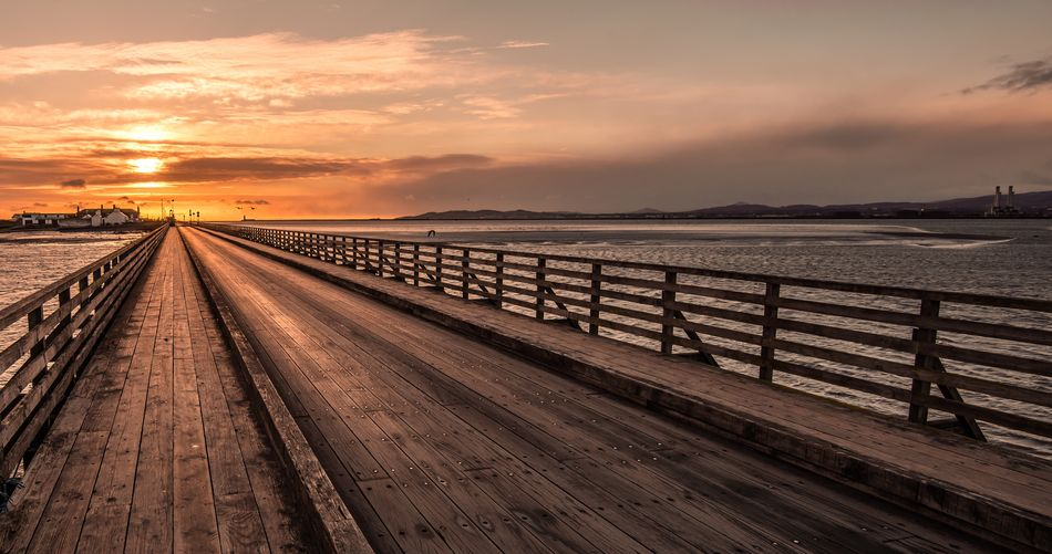 Wooden bridge against cloudy sky during sunrise