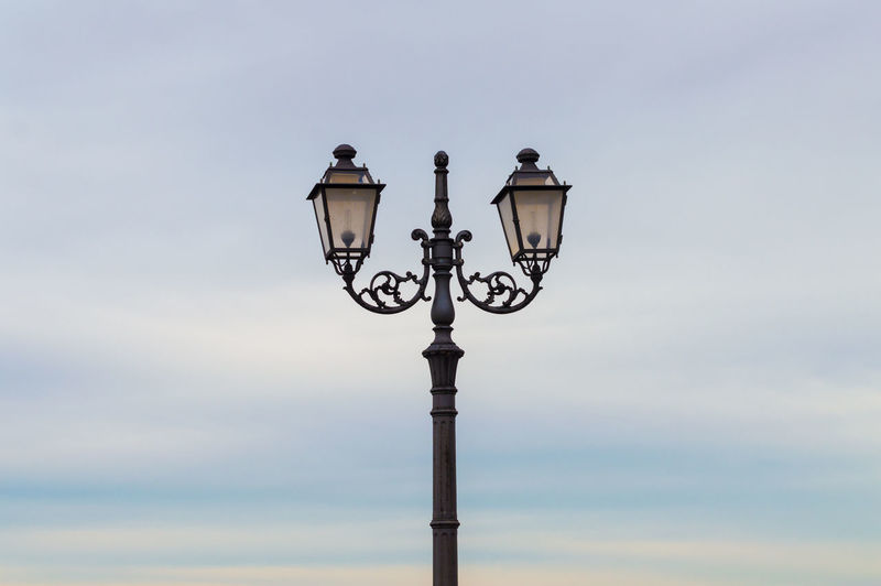 An ornate street lamp with double light made of wrought iron, in a beauty sky background. Street Light Lighting Equipment Sky Street No People Cloud - Sky Low Angle View Nature Electric Light Retro Styled Day Technology Outdoors Metal Electricity  Light Pole Gas Light Copy Space Antique Electric Lamp Electrical Equipment