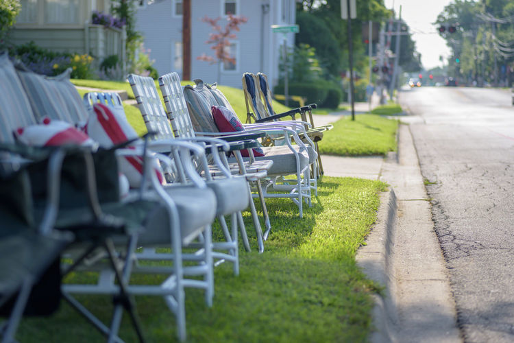 Empty chairs against grass
