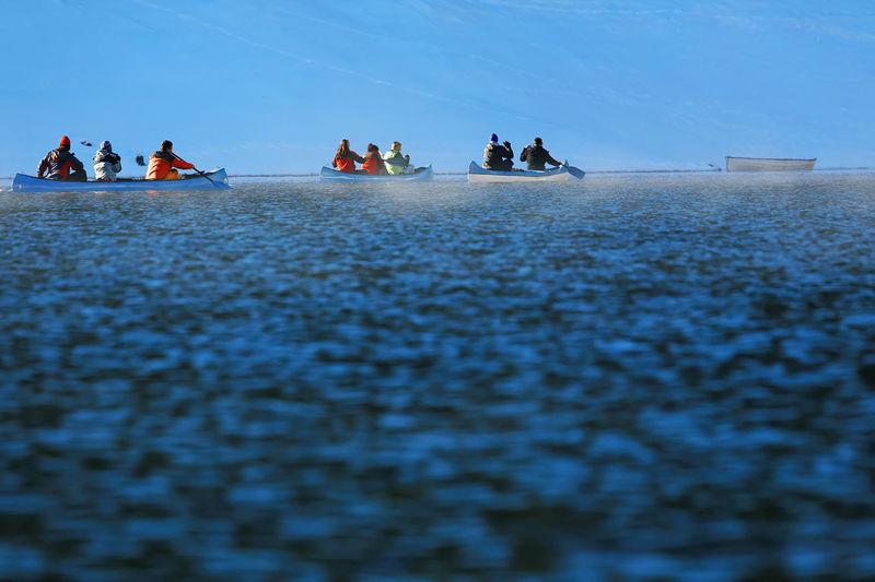 People in kayaks against sky