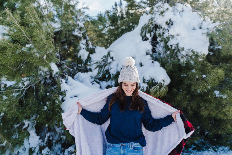 Woman wearing hat against trees during winter