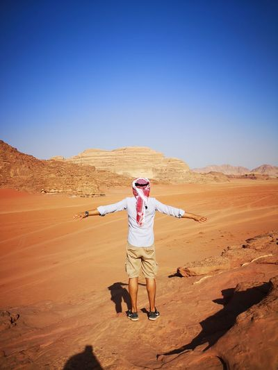 Rear view full length of man with arms outstretched standing at desert on sunny day