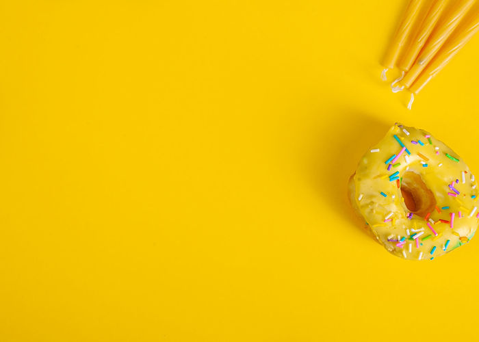 Directly above shot of multi colored candies against yellow background