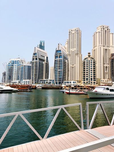 View Of Modern Buildings By River Against Clear Sky