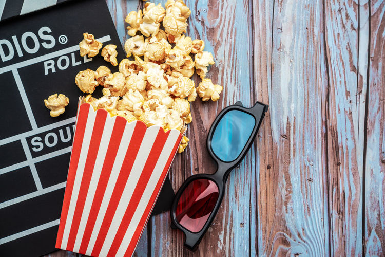 Popcorn with film slate and 3-d glasses on table