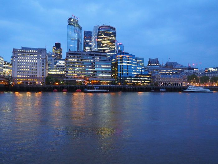 Illuminated buildings by river against sky in city at night