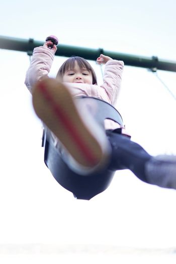 Low angle view of happy girl on swing