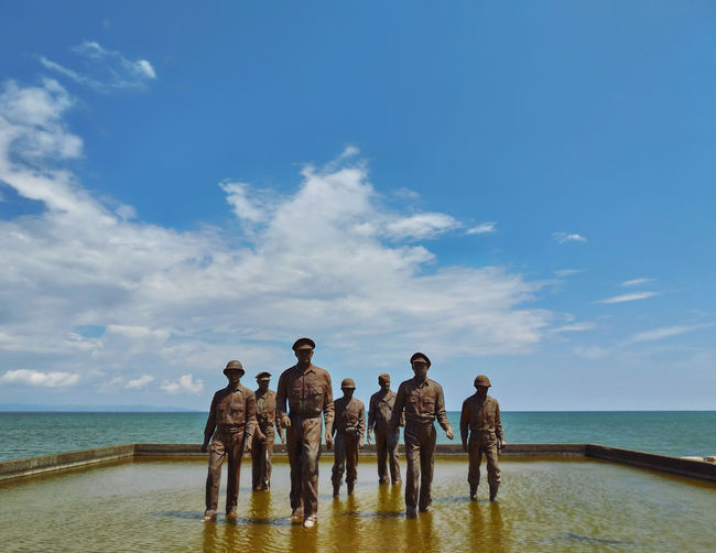 Rear view of people standing at beach against sky