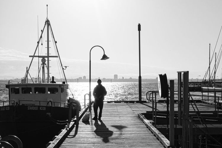 Rear view of man standing on pier