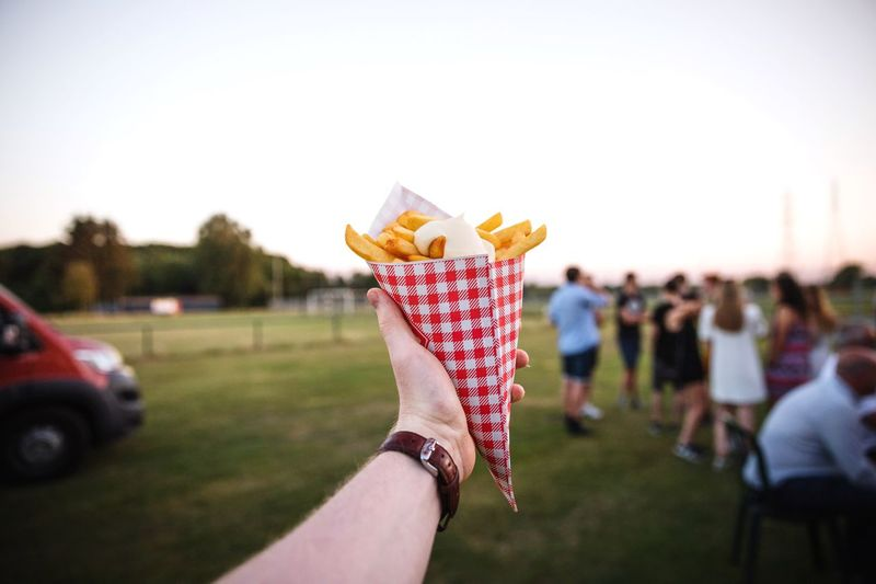 Close-up of french fries held by person in one hand