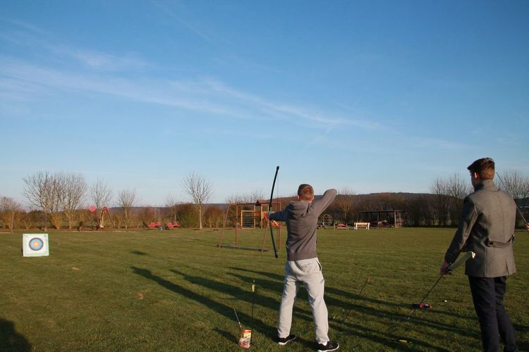 Rear View Of Men Shooting Arrows On Field Against Sky