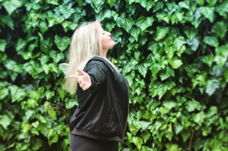 Side view of woman with arms outstretched standing against plants in park