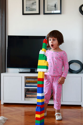 Girl looking at colorful stacked toys at home